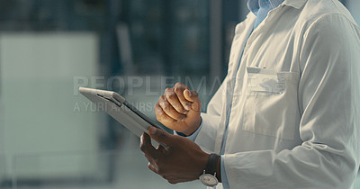 Buy stock photo Shot of a male doctor using a digital tablet in his office