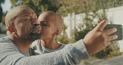 Buy stock photo Shot of a mature man and his grandson taking a selfie outside