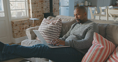 Buy stock photo Shot of a mature man working on his laptop at home