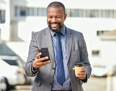 Buy stock photo Shot of a businessman holding his cellphone and a takeaway coffee while out in the city