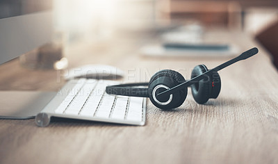 Buy stock photo Shot of a pair of headsets lying on the desk in an empty office