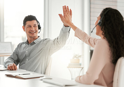 Buy stock photo Shot of two young call center agents giving each other a high five in an office at work