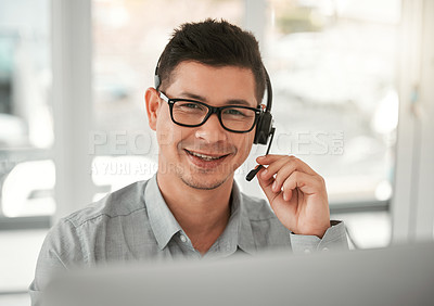 Buy stock photo Shot of a young male call center agent at work