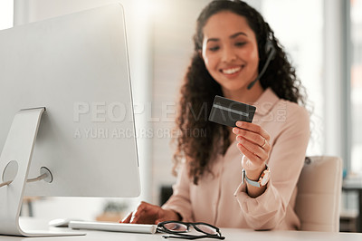 Buy stock photo Shot of a young female call center agent using a credit card at work