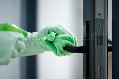 Buy stock photo Shot of a woman wiping down the handles on her door