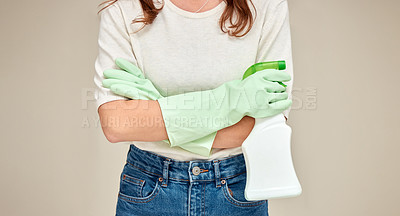 Buy stock photo Shot of an unrecognizable person standing with their arms crossed while holding a spray bottle against a white background