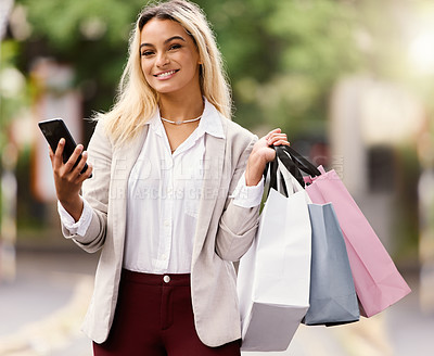 Buy stock photo Cropped portrait of an attractive young woman texting while out shopping in the city