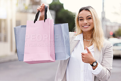 Buy stock photo Cropped portrait of an attractive young woman raising her bags and gesturing thumbs up while out shopping in the city
