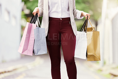 Buy stock photo Cropped shot of an unrecognizable young woman standing with her bags while out shopping in the city