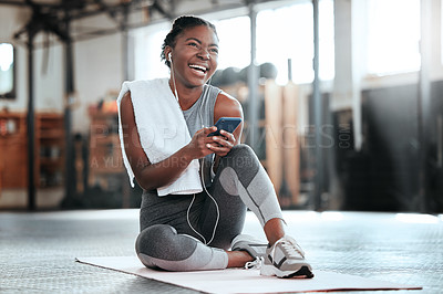 Buy stock photo Shot of a young beautiful woman using her cellphone and earphones after her workout at the gym