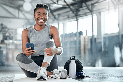 Buy stock photo Shot of a young beautiful woman using her cellphone after her workout at the gym