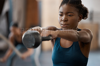 Buy stock photo Cropped shot of an attractive and athletic young woman working out with a kettle bell in the gym