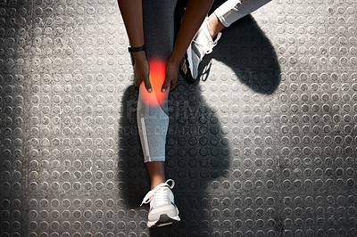 Buy stock photo High angle shot of an unrecognizable and athletic young woman holding her knee in pain while at the gym