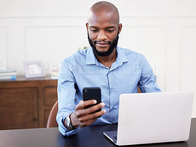 Buy stock photo Shot of a young businessman using his cellphone while sitting at his desk