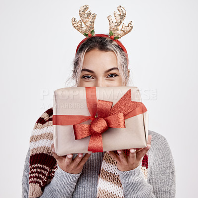 Buy stock photo Studio portrait of an attractive young woman holding a present up in front of her face while dressed in Christmas-themed attire