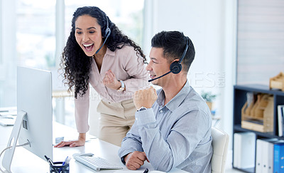 Buy stock photo Shot of two young call centre agents using a computer in the office during the day