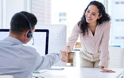 Buy stock photo Shot of a young call centre agent shaking her colleague's hand in the office during the day