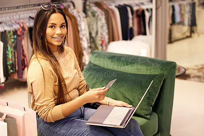 Buy stock photo Shot of a young woman using her credit card and a laptop while sitting in a boutique