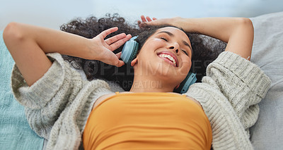 Buy stock photo Shot of a young woman lying down and enjoying the music