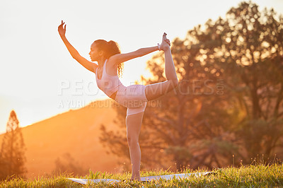 Buy stock photo Full length shot of an attractive young woman practicing yoga outside on a sunny morning