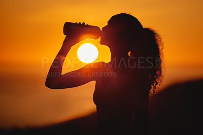 Buy stock photo Cropped shot of an unrecognizable and athletic young woman drinking water while exercising outside at sunset