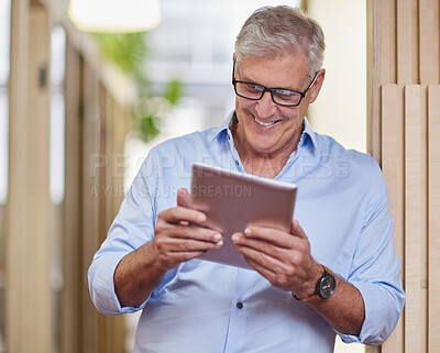 Buy stock photo Cropped shot of a handsome mature businessman using a table while standing in the hallway in his office