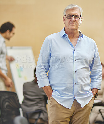 Buy stock photo Cropped portrait of a handsome mature man standing with his hands in his pockets in the boardroom with his colleagues in the background