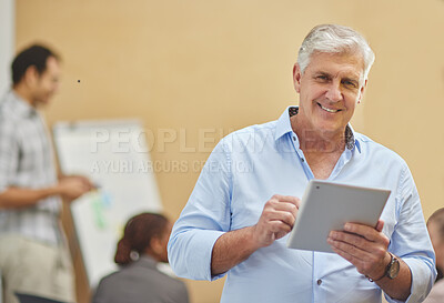 Buy stock photo Cropped portrait of a handsome mature man using a tablet in the boardroom with his colleagues in the background