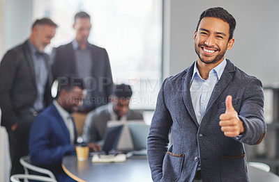 Buy stock photo Portrait of a young businessman showing the thumbs up in front of his colleagues having a meeting in the background