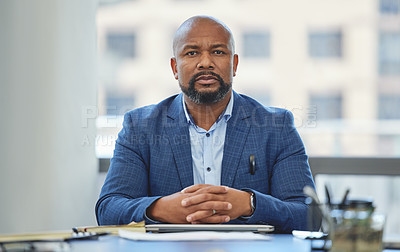 Buy stock photo Shot of a handsome mature businessman sitting alone in his office with his hands clasped
