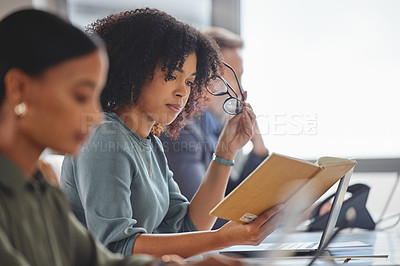 Buy stock photo Shot of a young businesswoman going through notes while working alongside her colleagues in a call centre