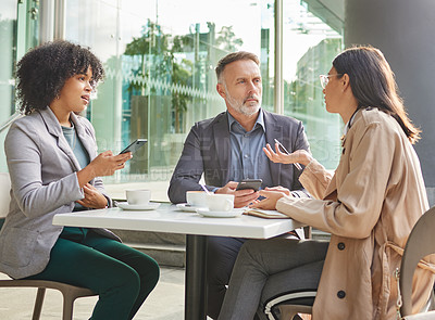 Buy stock photo Shot of a group of colleagues brainstorming ideas at a coffee shop while using their smartphones