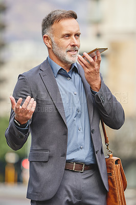 Buy stock photo Shot of a mature businessman using his smartphone to send a voice recording