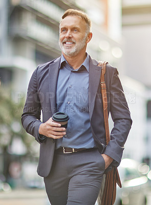 Buy stock photo Shot of a handsome mature businessman walking around town drinking coffee