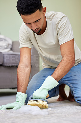 Buy stock photo Shot of a young man scrubbing the floor at home