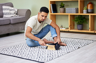 Buy stock photo Shot of a young man using a dustpan and sweeping his carpet at home
