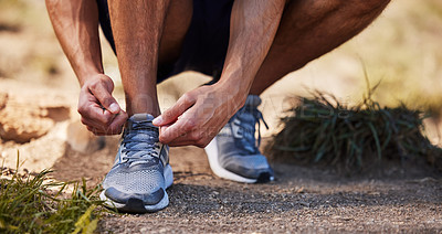 Buy stock photo Cropped shot of an unrecognizable man crouching down to tie his shoelaces before going on an outdoor run