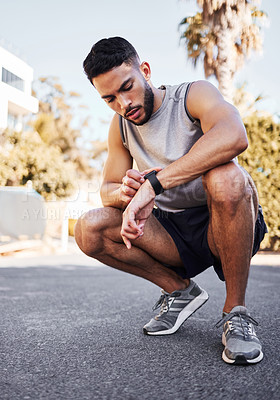 Buy stock photo Full length shot of a handsome young man crouching down and setting a timer on his watch before running outside