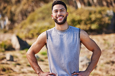 Buy stock photo Shot of a handsome young man standing alone outside with his hands on his hips after a run