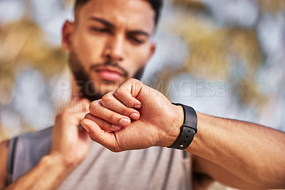 Buy stock photo Shot of a young man standing alone outside and using his watch to time his pulse after a run