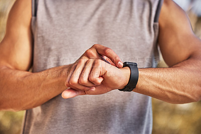 Buy stock photo Cropped shot of an unrecognizable man standing alone and setting a timer on his watch before running outside