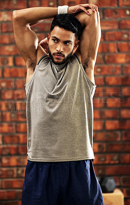 Buy stock photo Shot of a young man stretching before his workout in the gym