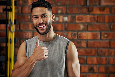Buy stock photo Shot of a young man showing thumbs up in the gym