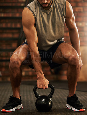 Buy stock photo Shot of an unrecognisable man working out with a kettle bell in a gym
