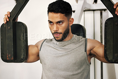 Buy stock photo Shot of a young man working out with a chest press in a gym