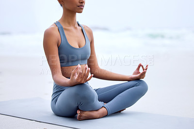 Buy stock photo Cropped shot of an unrecognizable young woman meditating while practicing yoga on the beach