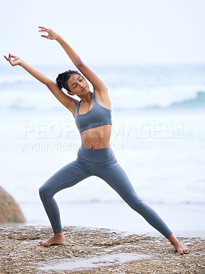 Buy stock photo Full length shot of an attractive young woman practicing yoga on the beach