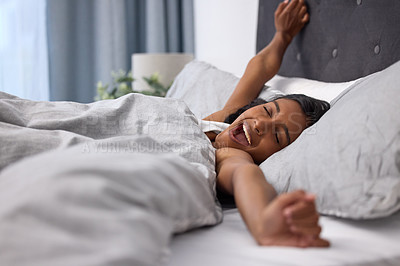 Buy stock photo Shot of a young woman yawning and stretching while lying in her bed