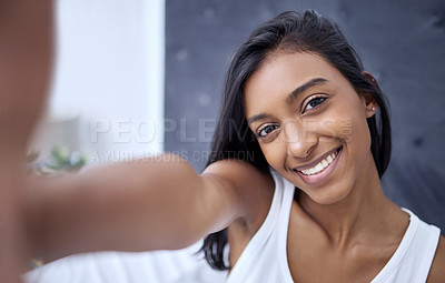 Buy stock photo Shot of a beautiful young woman taking a selfie at home