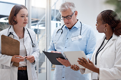 Buy stock photo Shot of a team of doctors reading through medical information together